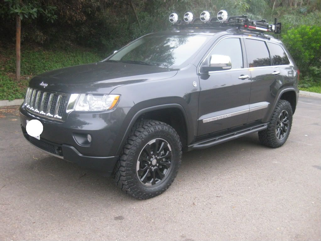 2012 Jeep Grand Cherokee with black wheels and roof rack
