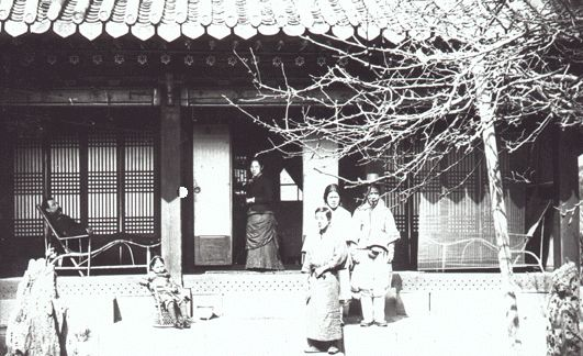 Family in front of Korean house. Probably Percival Lowell in chair on porch. Japanese cook? ca. 1889