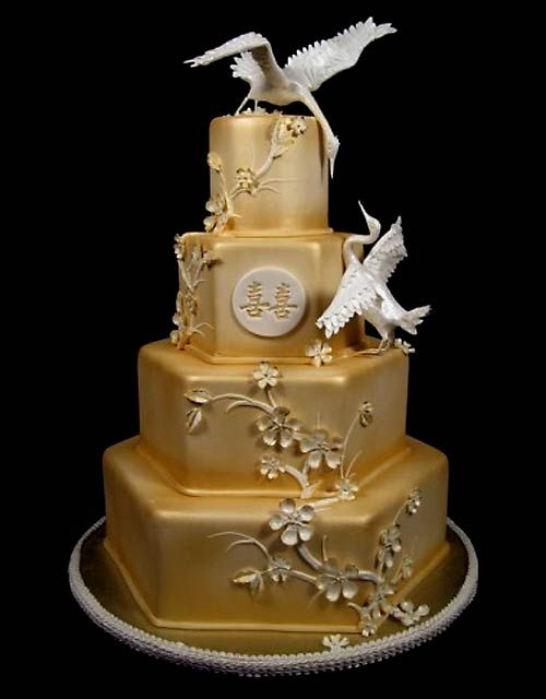 Four tier hexagon Asian style gold wedding cake decorated with gold cherry blossom decorations and two birds wedding cake topper representing the bride and groom.