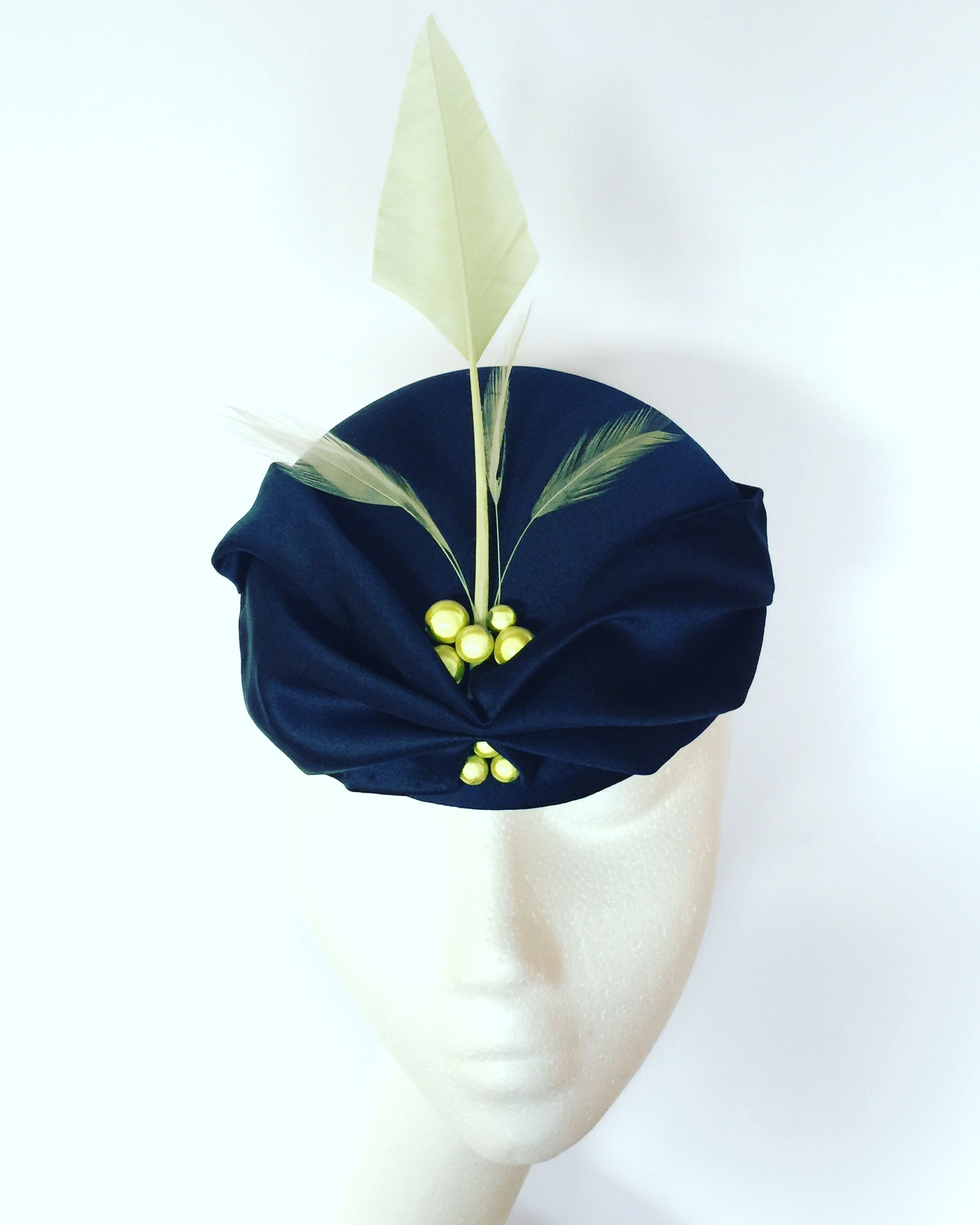 Navy base with draped fabric, lime green quill, feather and beading. Small hat perfect for a wedding guest or day at the races.