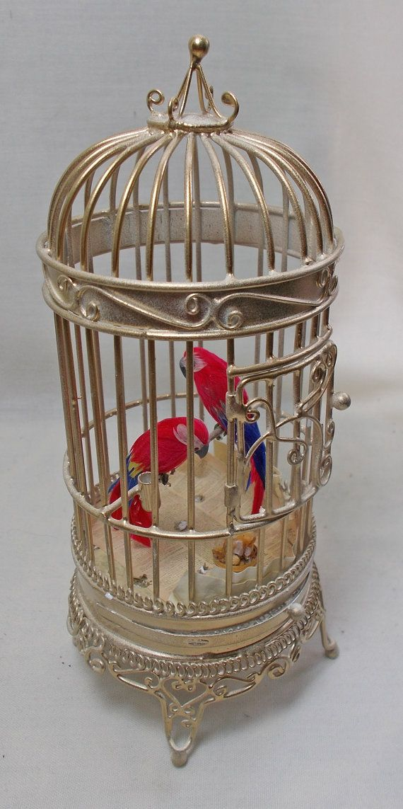 Dolls house miniature Floor Standing Guilded Gold Cage with two feathered Macaw's  named Romeo & Juliet. The birds are fixed in place. The door opens. The bottom tray is fixed closed as I have lined it with newspaper, a tray of seeds and some bird droppings for authenticity!. H16cm x W6.3cm x D6.3cm Z