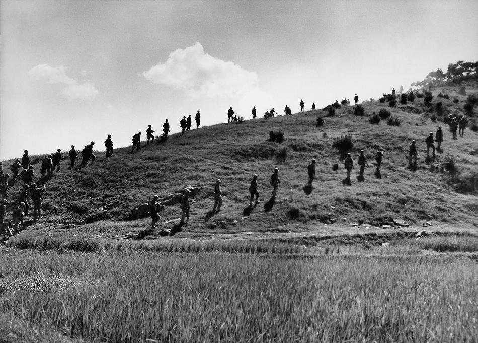 Marines of the United states are moving along a hill in South Korea. June 25, 1950