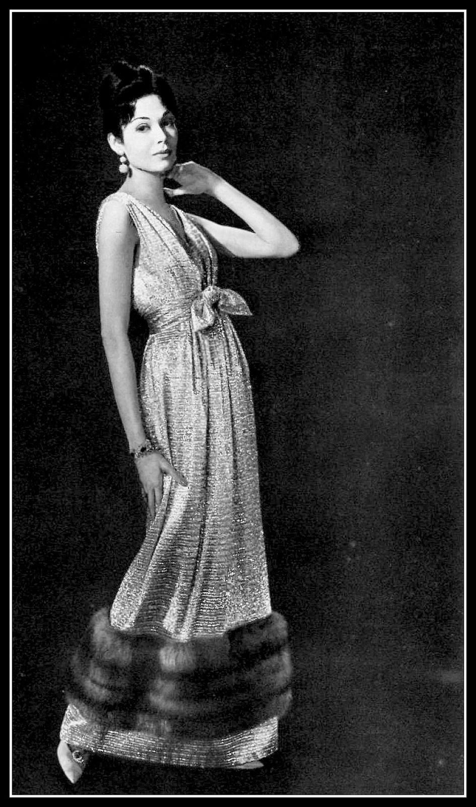 Model in silver lamé evening dress, banded in sable at the hem, by ...