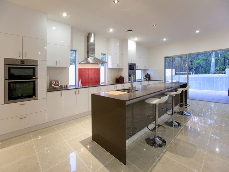 Lovely Open Space With A Narrow Kitchen Island And Beige Tiles