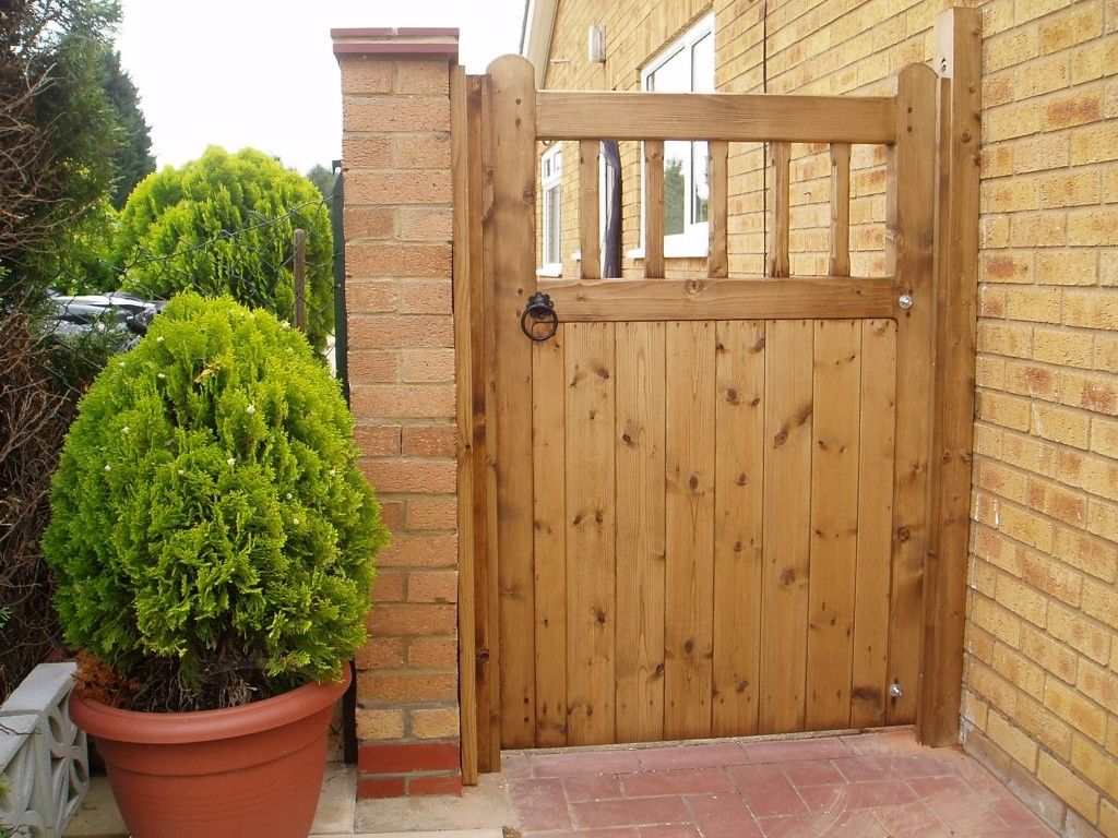 outstanding brown color gravely shape wooden gate and combine with brown color bricks wall also green