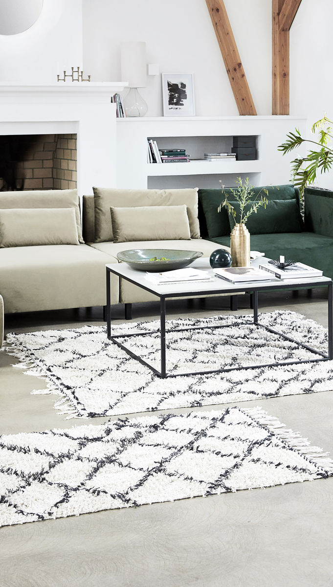 Soft white rug with black diamond pattern and tassels