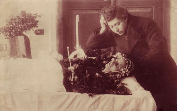 Memento Mori: Woman laid out with family member looking over her.