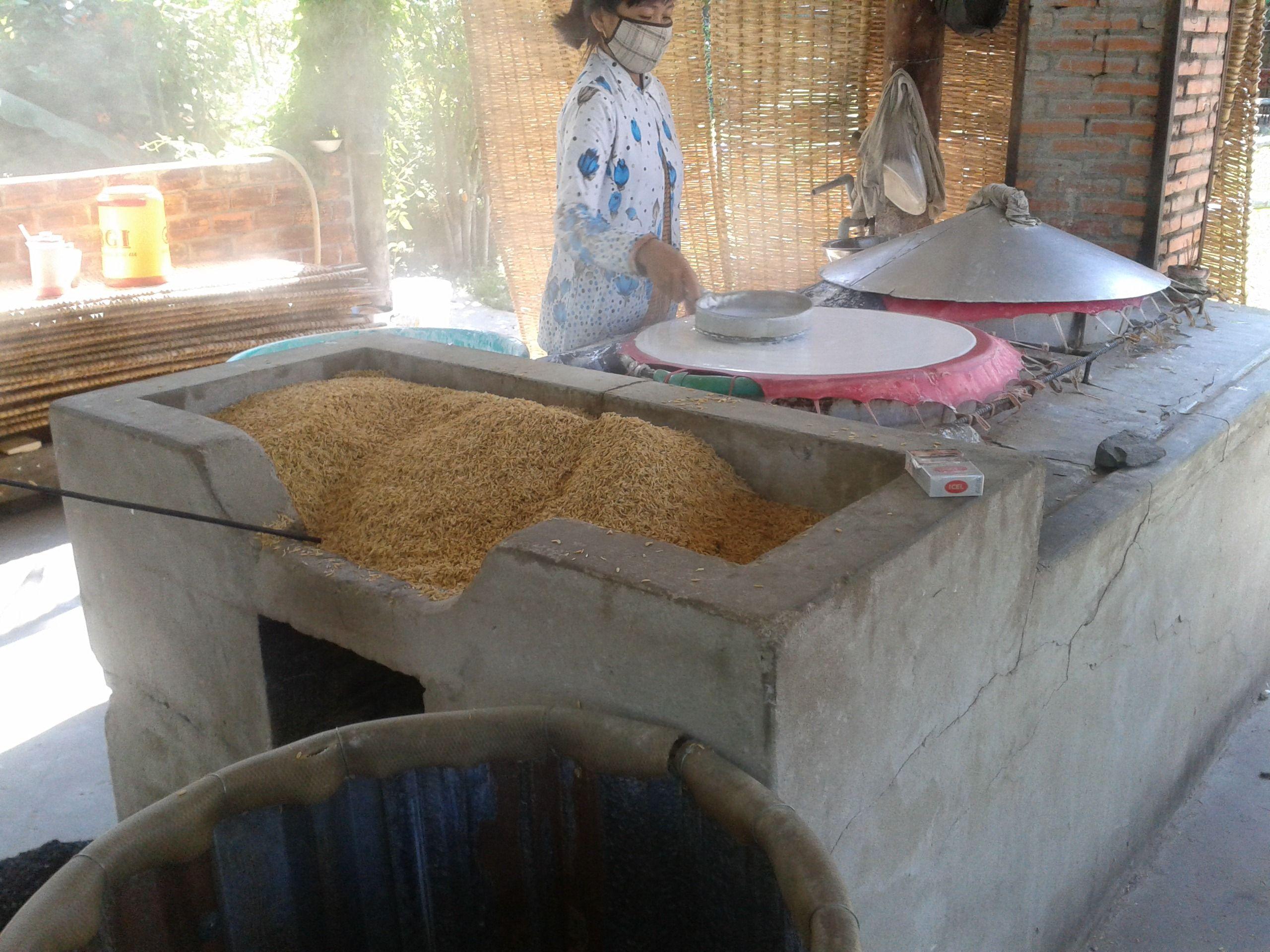 Voordat de rijst noedels wordt opgedroogd, wordt het gebakken op een warme kookplaat.