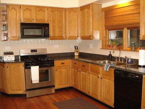 Brown Oak Kitchen Cabinet Connected By Black Granite Countertop And Beige Tile Backsplash Also Stainless Steel Curved Faucet Splendid Designs With
