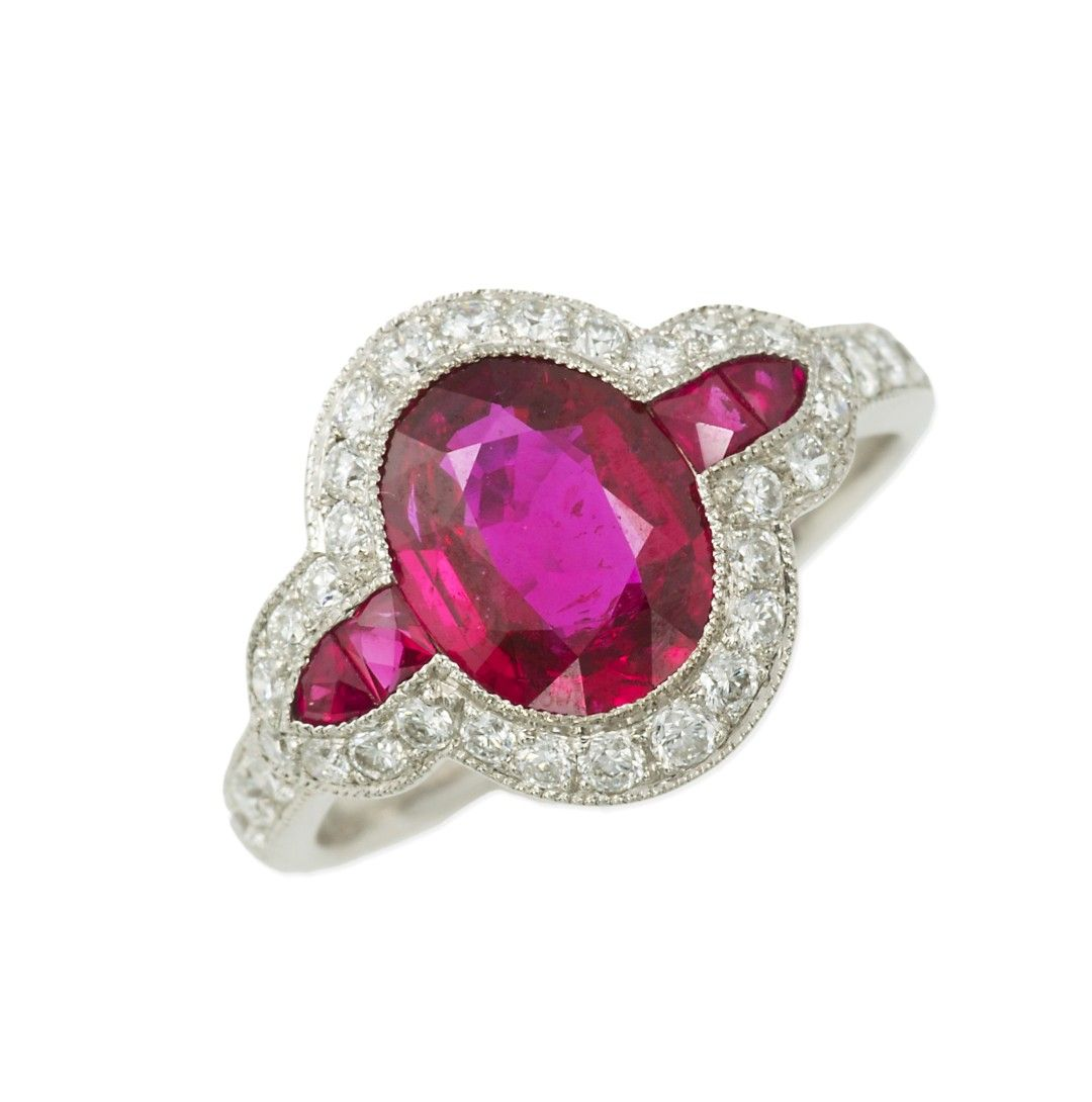 Platinum setting, with central oval ruby 1.99cts, GRS report; vivid red colour with no indication of thermal treatment. Flanked either side with 1 square- and 1 trillion-cut ruby. Further set to the border of the cluster with a round brilliant-cut diamond, approx total diamond weight 0.55cts