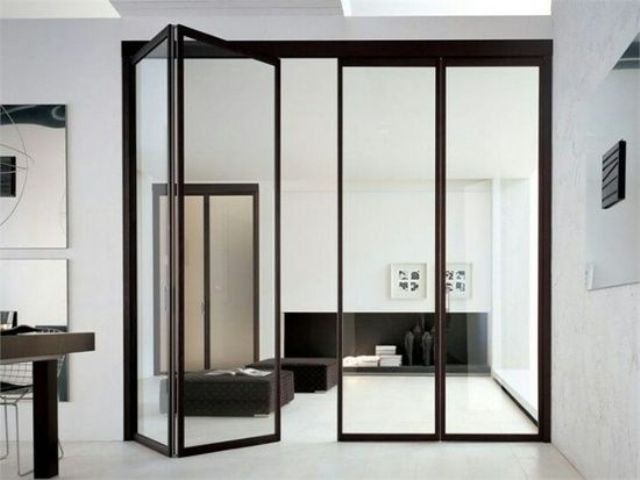 folding black frame glass doors separating the kitchen and the ...