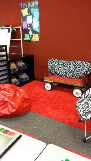 An old wagon with a cushion makes a popular seat in a classroom library.  The handle has been removed and a strip of wood over the wheel prevents it from rolling.