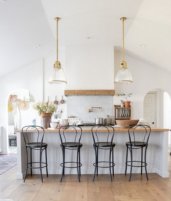 Eclectic Home Tour Seeking Lavender Lane - tour this rancher turned farmhouse with touches of European flair. Love this open concept kitchen with classic black bistro chairs and brass lighting #kitchen #whitekitchen #farmhousekitchen #farmhousedecor #eclectickitchen #kitchenlighting #brasslighting #kitchenrenovation #hometour #housetour #interiordesign