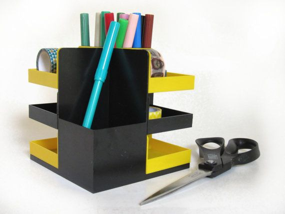 A vintage desk organizer in yellow and black plastic for pen, pencil & office knick knacks storage. Made in the 1960s when plastic was very hip and happening! Would also make a terrific accessories and jewellery storage unit (365vintage.etsy.com).