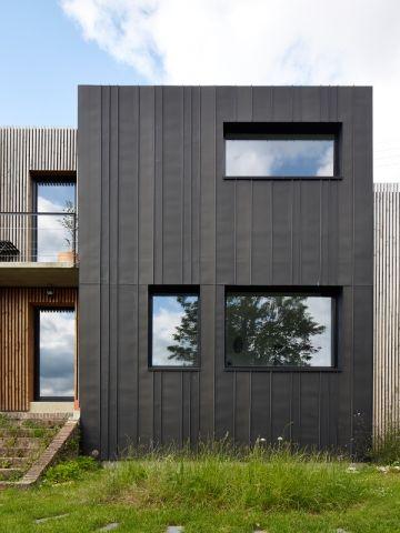 Une maison en zinc noir pos e sur un mur en brique mur for Maison moderne zinc