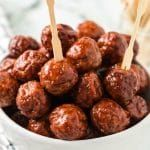 Grape Jelly Meatballs (Crockpot Recipe)-   Made in the crockpot, these easy three-ingredient grape jelly meatballs are the perfect appetizer for any gathering!       With only three easy ingredients, these simple, sweet and savory crockpot meatballs have forever been a staple at parties. Frozen meatballs, grape jelly and barbecue sauce are mixed and simmered in the slow cooker to make this deliciousappetizer.  Don't miss our crockpot Swedish meatballs and our buffalo meatballs for more meatbal #meatballswithgrapejelly