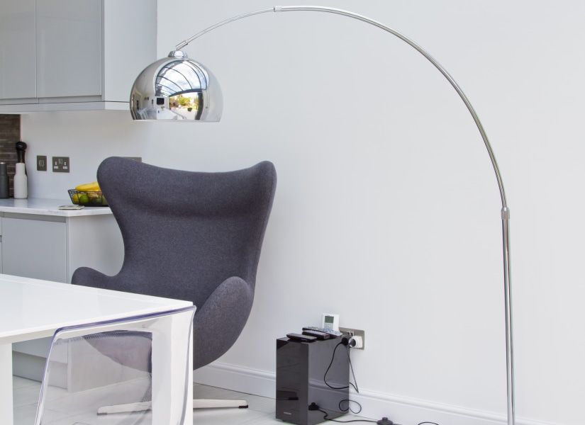The Stylish Bow Floor Lamp With An Adjustable Arching Stem And An Articulated Chrome Spheri