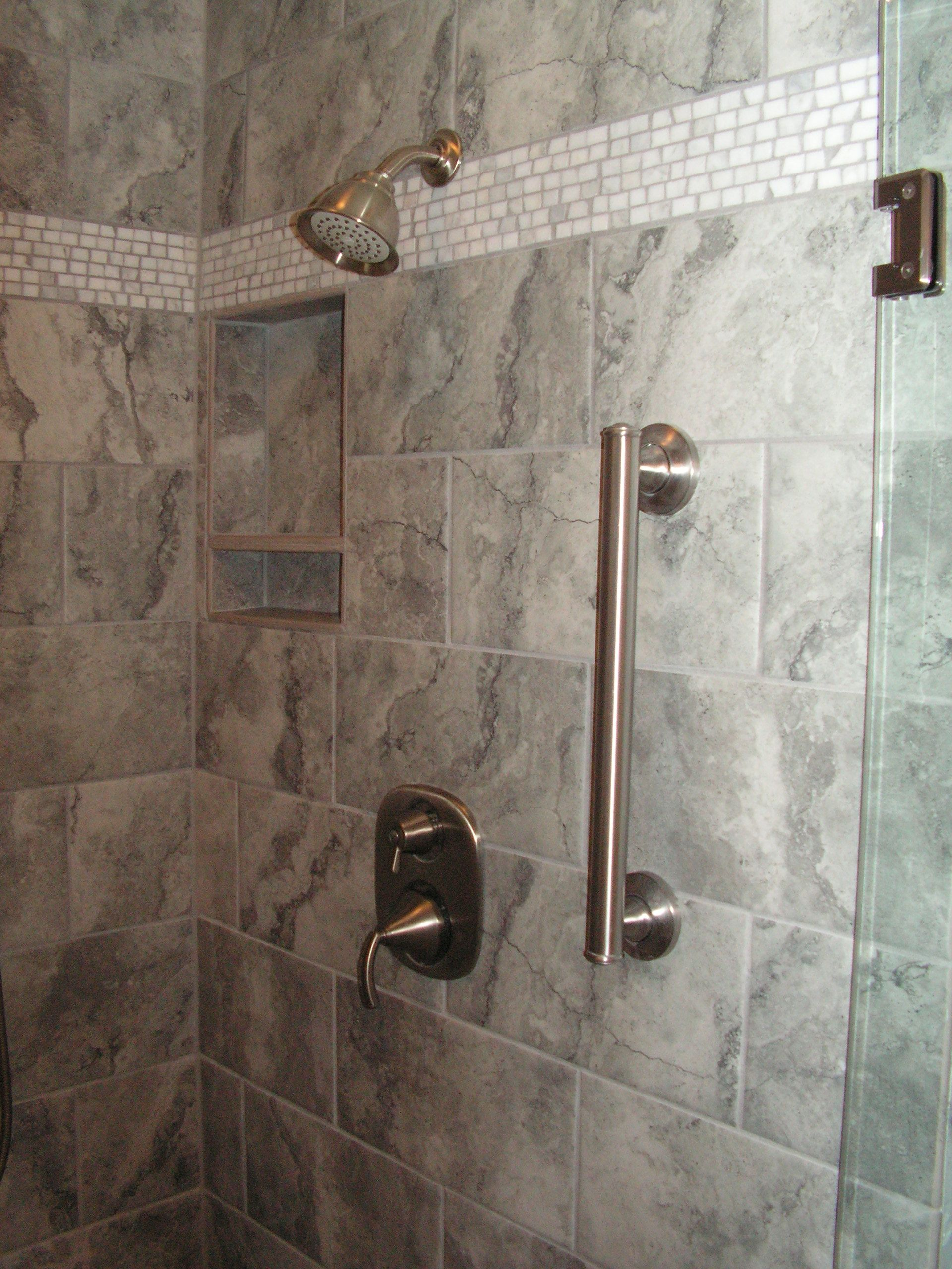 Shower remodel close up showing recessed shower caddie and grab bar ...