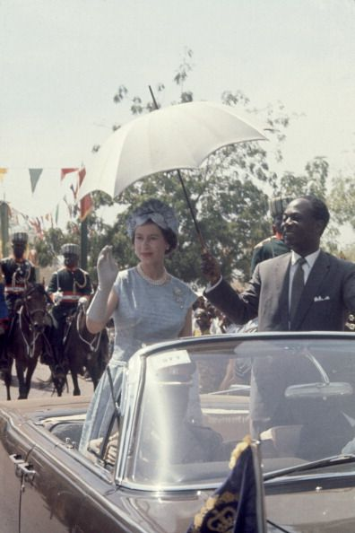 While on a Royal Visit Queen Elizabeth II waves to spectators as President of Ghana Kwame Nkrumah holds an umbrella to shade her as they enter a...