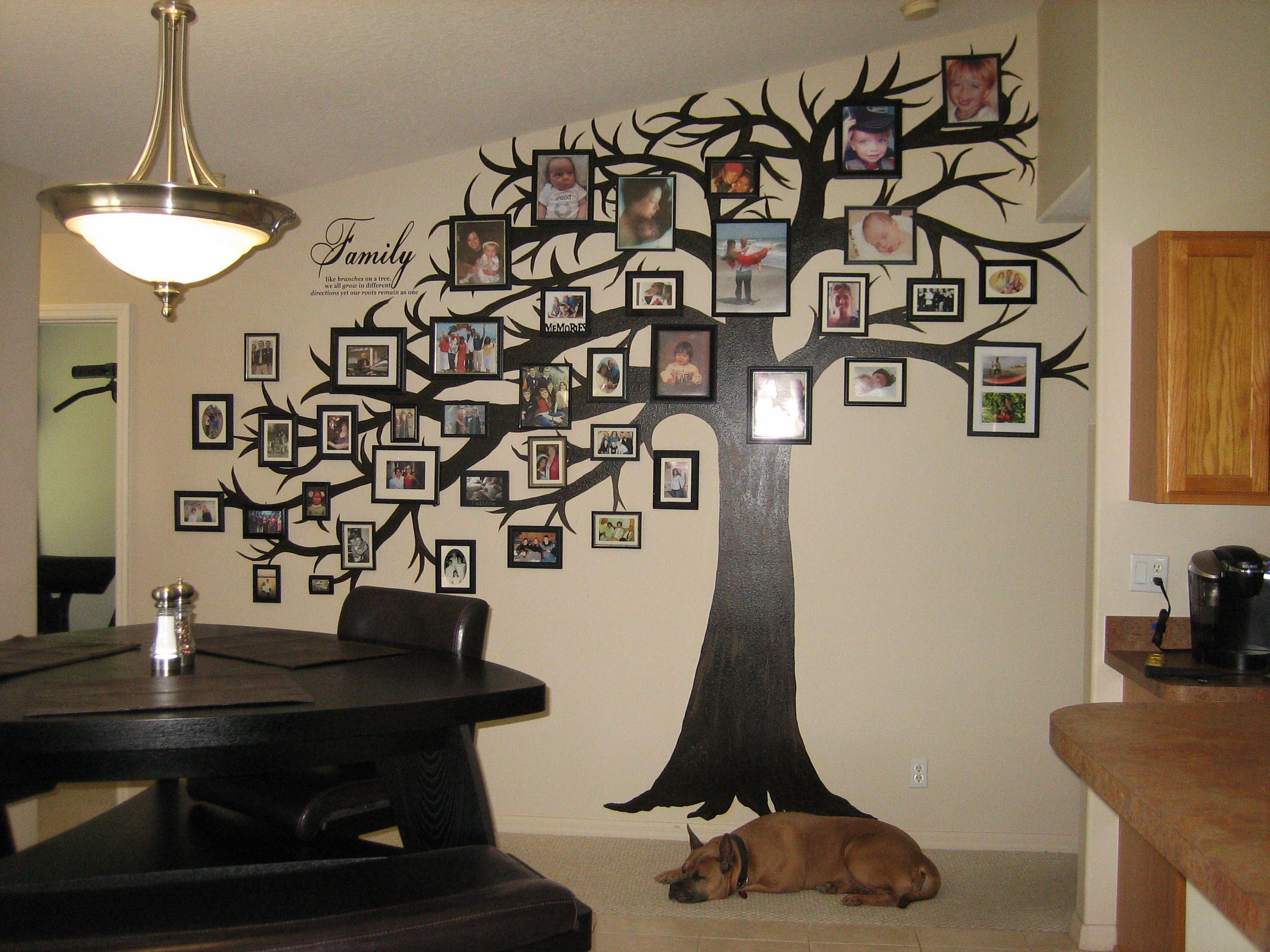 Tree painted on an irregular shaped wall with miscellaneous picture ...