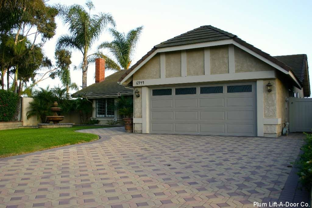 this home has a stucco exterior and a gray garage door white trim borders the garage the dark