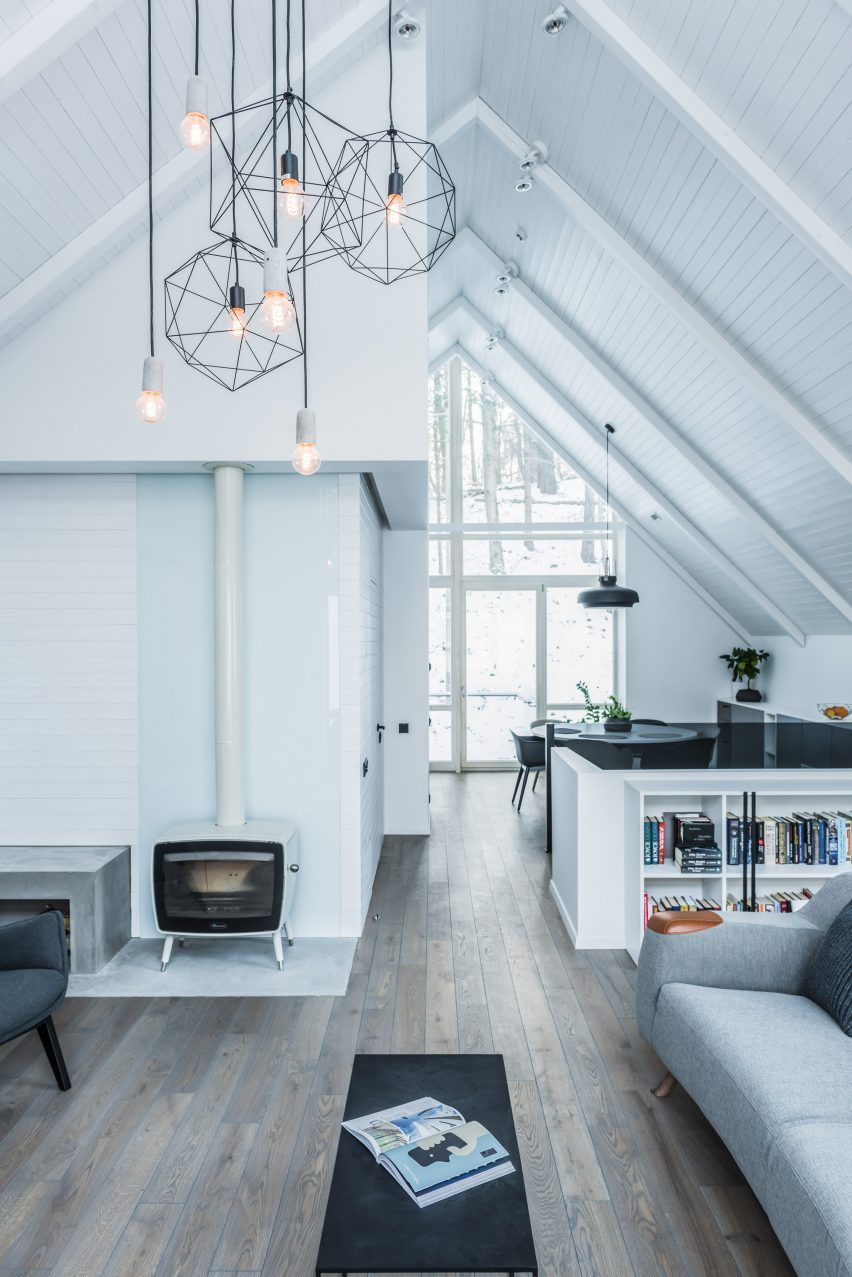 Minimal interiors draw focus to the snowy forest surroundings inside