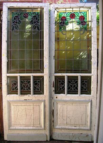 A pair of painted 19th century French leadlight doors decorated with lead-light coloured glass arranged into floral and geometric patterns & A pair of painted 19th century French leadlight doors decorated ...