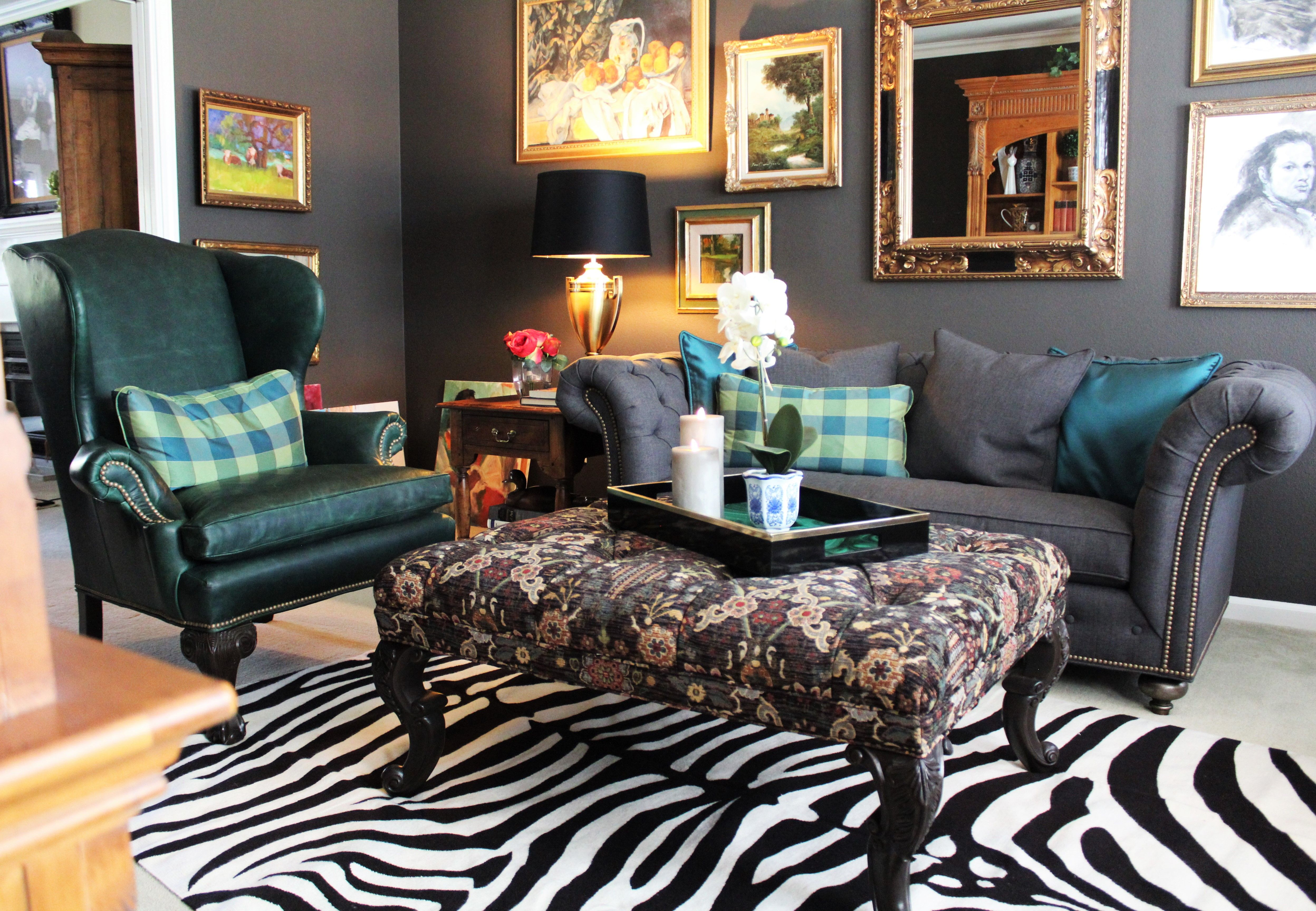 Giles chair in green waxed leather , Mansfield sofa, tapestry bench and Zebra rug and Salon style hangings to add a bit of whimsy to the somber  Black Fox -Den