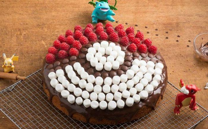 eine tolle schoko pokemon torte mit weißem pralinen und roten himbeeren und drei kleinen pokemon wesen und pikachu