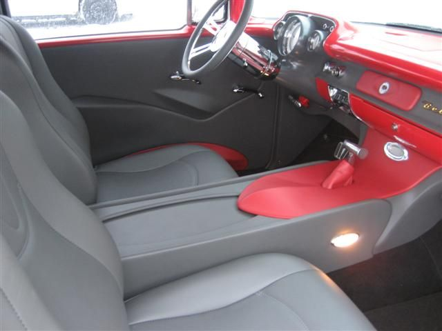 57 Chevy - Grey & Red Leather interior, Mercedes Carpet  We used a set of our StreamLine Sport Bucket Seats in this car, and built kustom rear bucket seats. A full length console was fabricated that stretches from the dash, all the way back to the package tray. The console has a sliding door inbetween the seats to access switches and a storage area. The door panels feature hand formed fiberglass arm rests that give the doors a clean, sleek feel. We used our woven for speaker grilles. The…