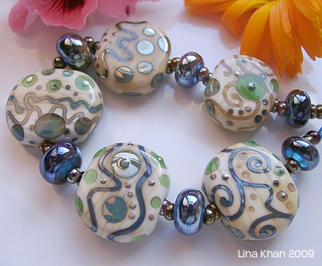 Ivory squeezed beads are softly silvered with D-Helix Elektra, Gaia, Kronos and Khaos. Spacers are encased with blue shimmering Triton ~~ The squeezed beads are