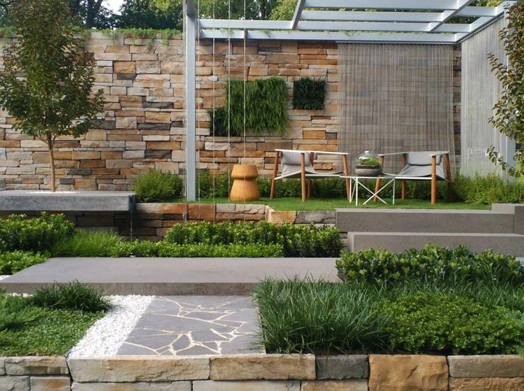 clôture de jardin en pierre naturelle, pergola en métal dotée de voilages et un coin lounge cosy