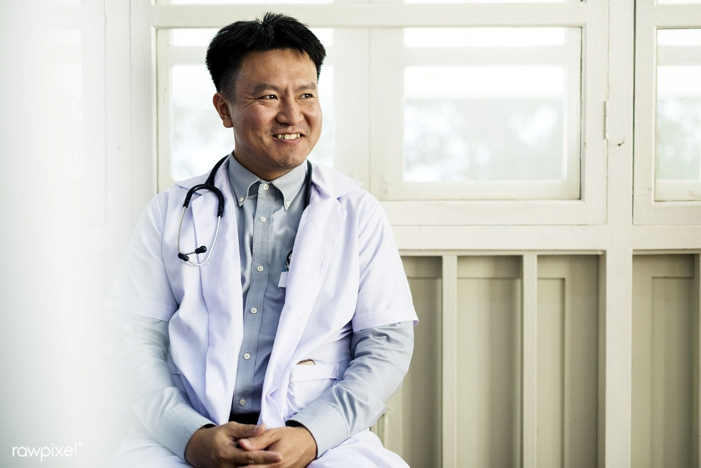 Download premium photo of An Asian doctor working at a