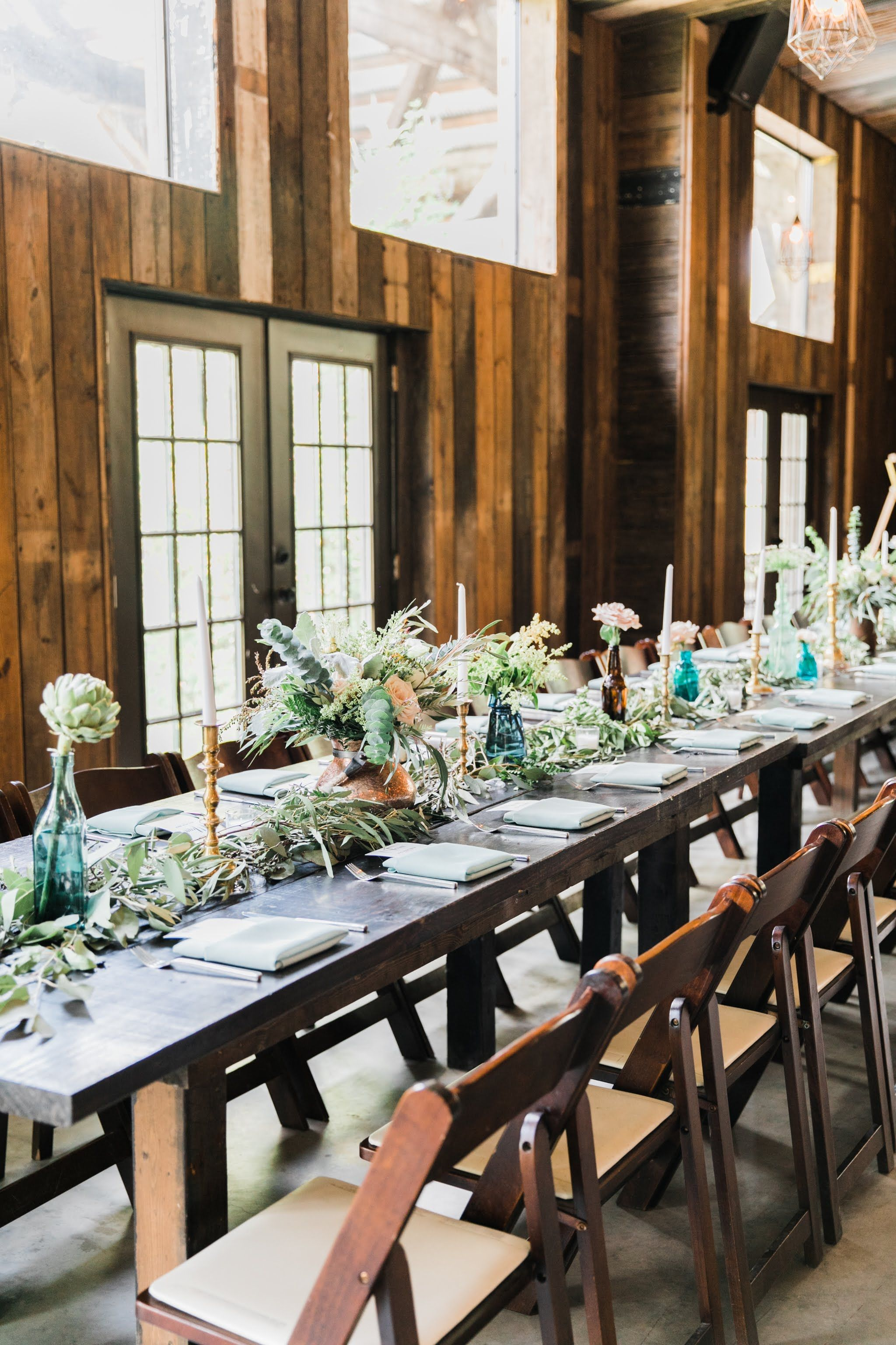 Runners with greenery on dark stained farm tables are our