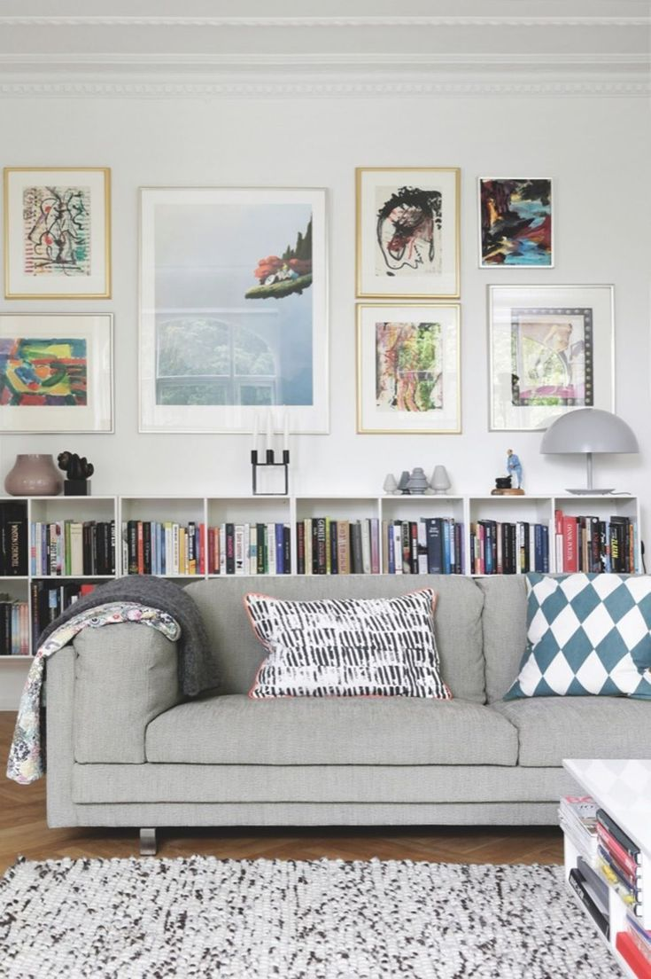 Home Interior Design Grey Sofa In Front Of Books And Paintings