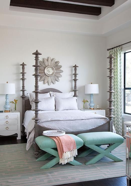 Chic bedroom boasts a tray ceiling lined with rustic wood beams placed over a silver sunburst mirror placed over a gray 4 poster bed, Noir Ferret Weathered Bed, dressed in white and gray print bedding flanked by white nightstands accented with gold ring pulls, Bungalow 5 Jacqui 3 Drawer Side Table, and baby blue lamps.
