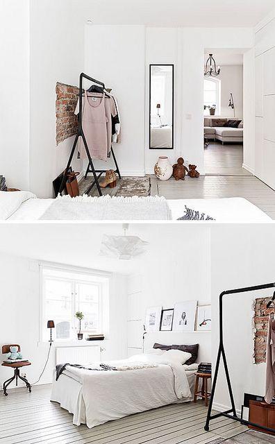 Une jolie décoration de chambre avec des murs blancs des vêtements sur un portant