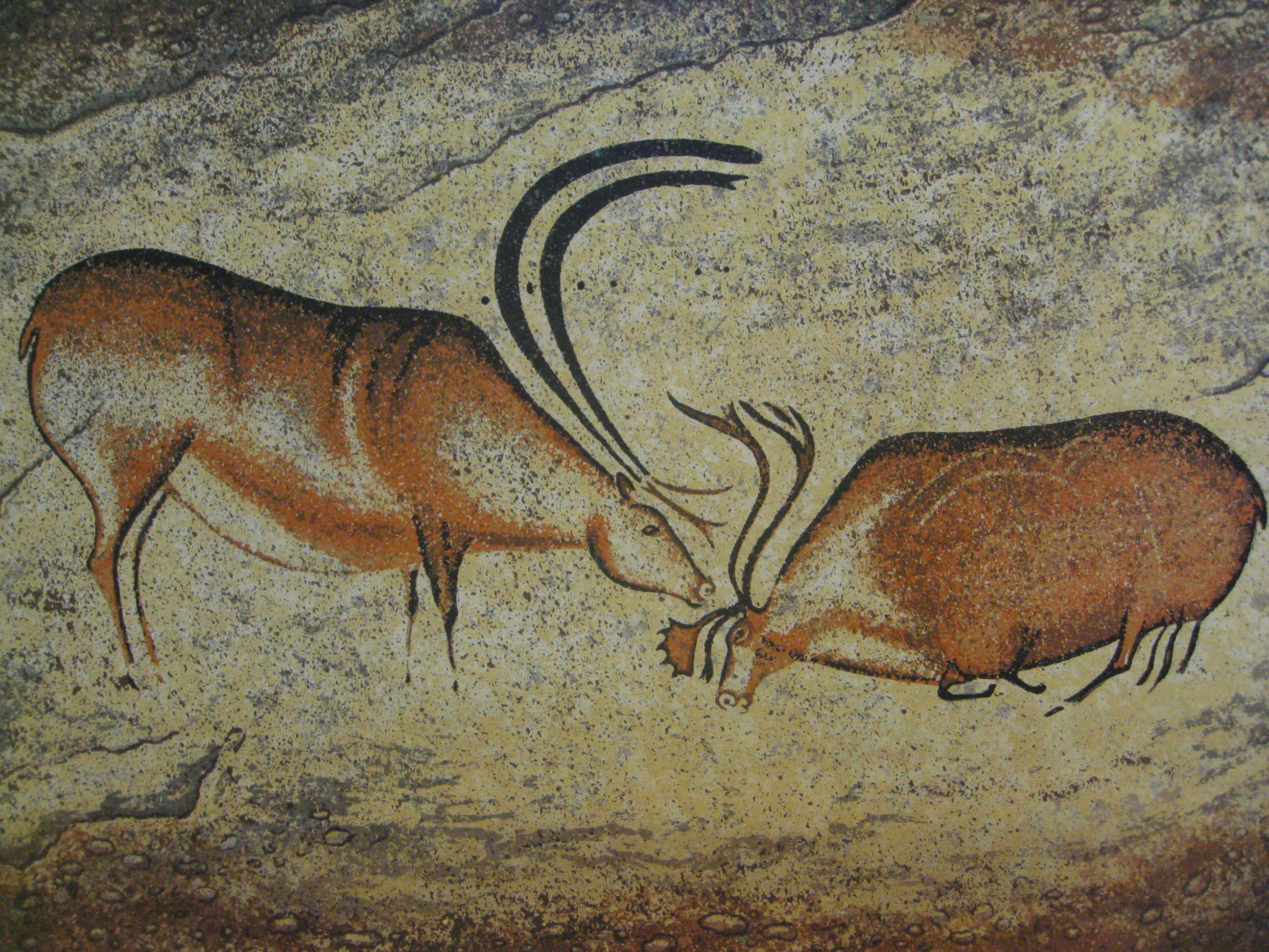 Two deer, one is a stag with large antlers, while another, with smaller antlers is kneeling before it.