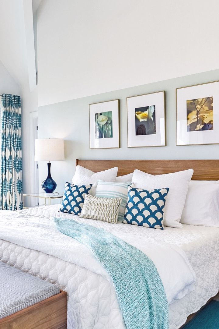 Beach house bedroom with teal accents. Half wall is ...