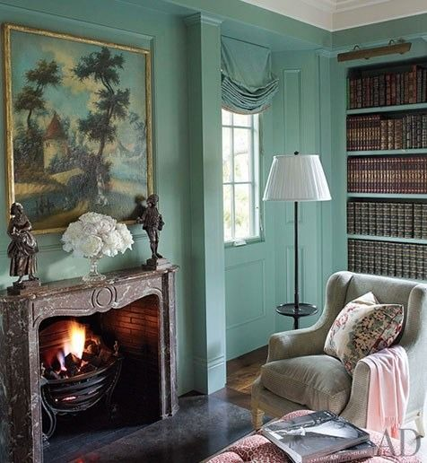 A landscape painting overlooks the library, whose walls are painted in Benjamin Moore's Stratton Blue | archdigest.com