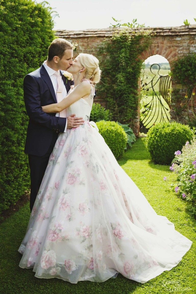 bride & groom kiss by the Angel Gate at Birtsmorton Court, floral ...