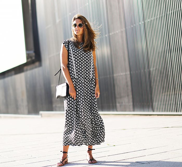 Blogger Clochet wears a black and white maxi dress with lace-up sandals, crossbody bag, and round sunglasses