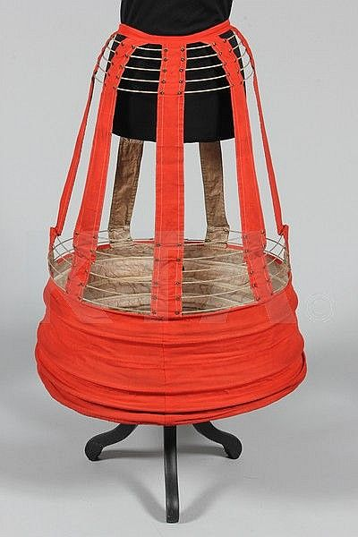 A Medici cage crinoline 'with improver', late 1860s-early 1870s, stamped 'R.Gates, Regd 37 Old Change', of scarlet wool lined in checked glazed cotton, with metal struts