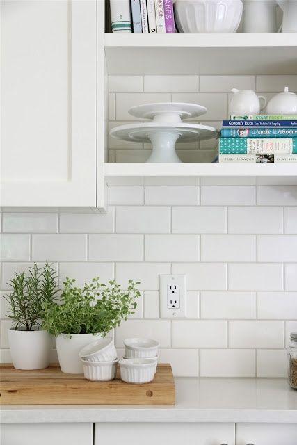 I also like how the butcher block cutting board and plants bring a cozy,  warm vibe to the space. This is standard white subway tile ...
