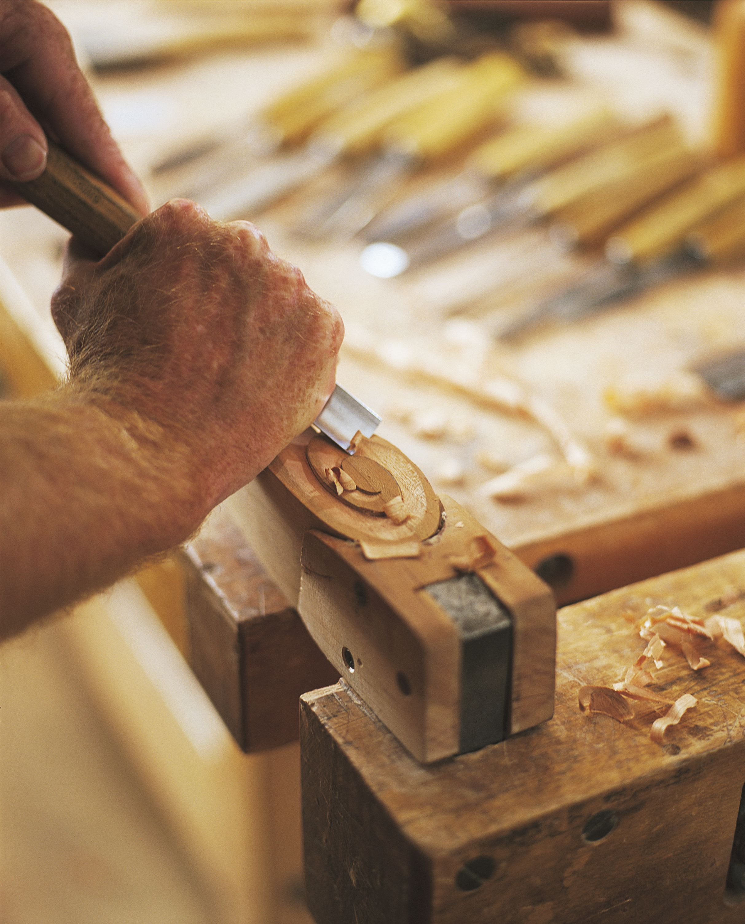 Chip carving a curl on the arm of a sophias dining chair in the