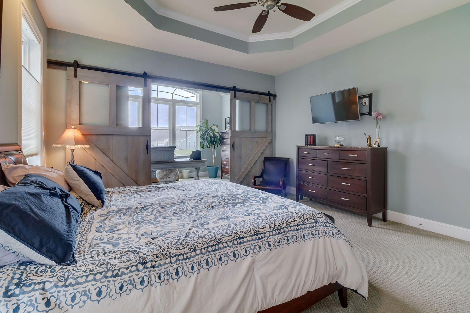 The sliding barn doors and tray ceilings in this Master ...
