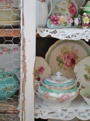 chicken wire cabinet with vintage rose dishes