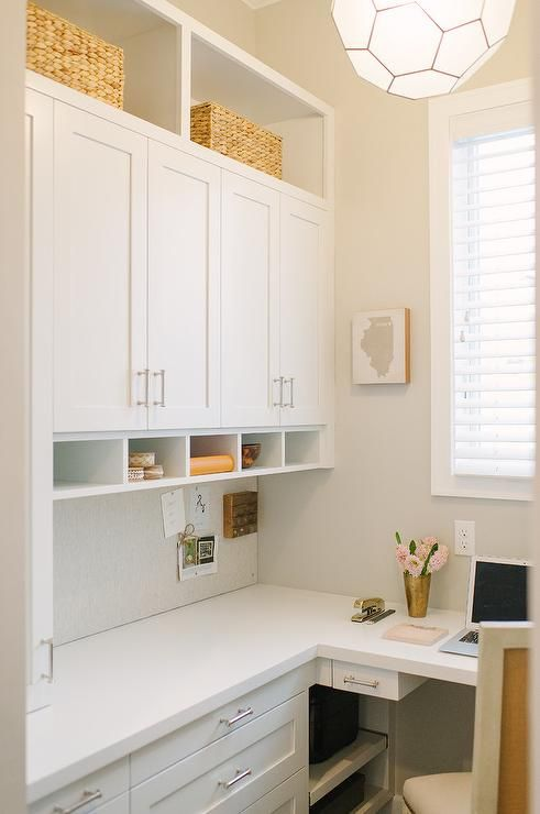 A White Built In L Shaped Desk Is Accented With Nickel Pulls And A