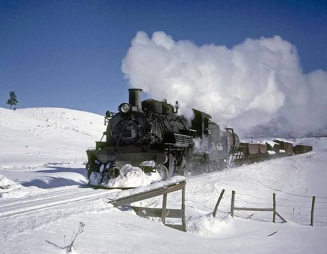December 1961. The whistle is blowing for the busy crossing of highways 84 and 64, just before entering Monero canyon. This train doubleheaded from Chama to Azotea, and the helper has already passed by running light from Azotea to Gato, where he'll wait for the train to catch up for the climb to Falfa.