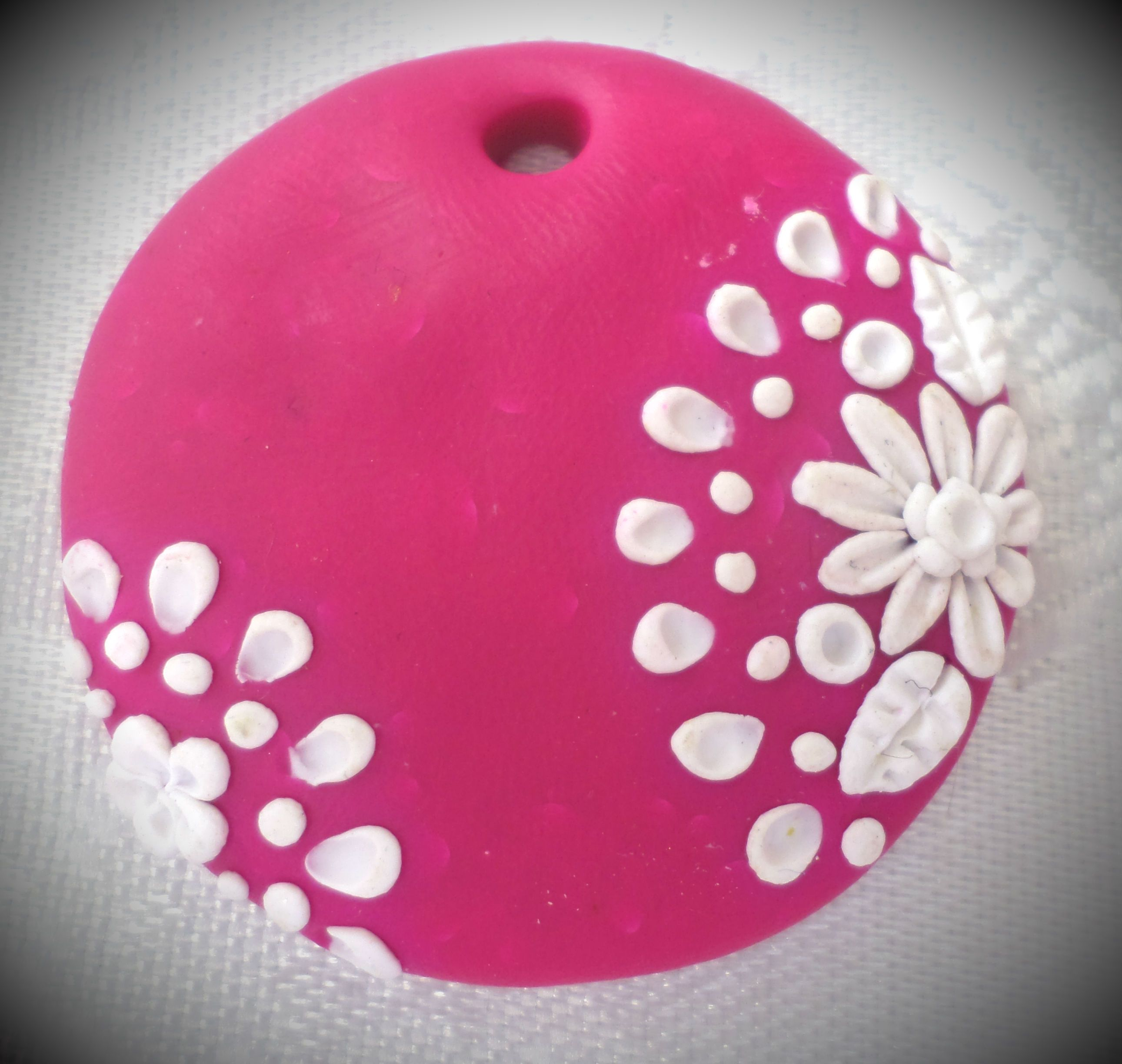 Polymer clay pendant, handmade with applique technique, one of a kind. Vibrant pink with lacy white flowers, leaves and dots. By Lis Shteindel.